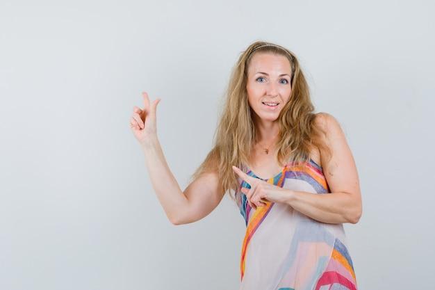 Blonde dame im sommerkleid zeigt mit den fingern weg und sieht fröhlich aus