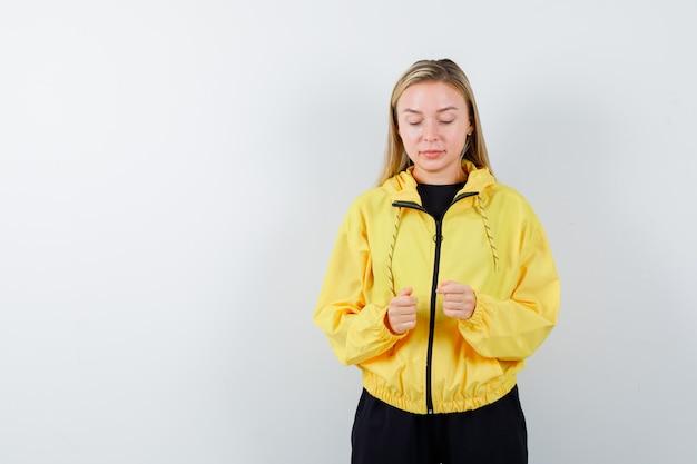 Blonde dame im trainingsanzug, die vorgibt, auf smartphone zu tippen und beschäftigt, vorderansicht schaut.