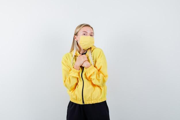 Blonde dame im trainingsanzug, maske, die hände auf brust hält und freudig schaut, vorderansicht.