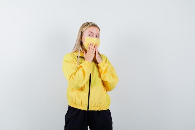 Blonde dame im trainingsanzug, maske, die hände auf mund hält und überrascht, vorderansicht schaut.