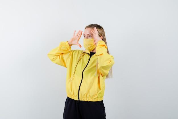 Blonde dame im trainingsanzug, maske, die mit den händen in der nähe des kopfes weit weg schaut und verwundert aussieht, vorderansicht.