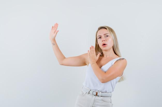 Blonde dame im unterhemd, hose zeigt karate-chop-geste und sieht selbstbewusst aus