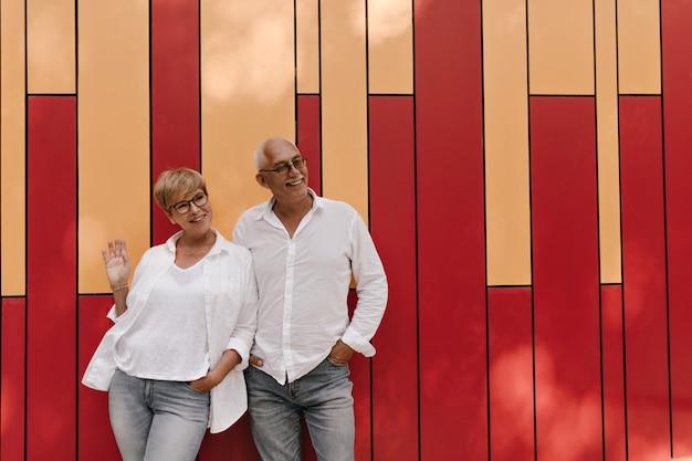Blonde dame in brille und helle kühle bluse, die mit altem mann im weißen hemd und in den jeans auf orange und rot lächelt und posiert.
