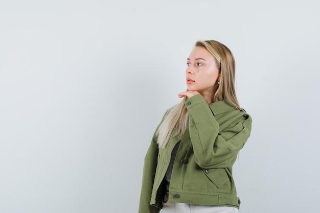 Blonde dame in der jacke, die hand unter kinn hält und nachdenklich, vorderansicht schaut.