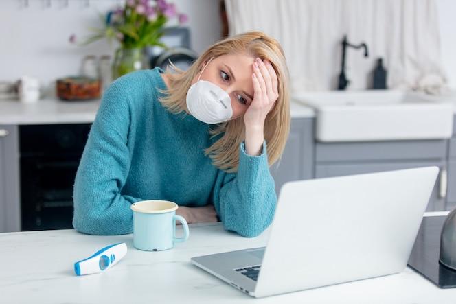 Blonde dame in der maske mit tasse getränk, thermometer und laptop-computer an der küche
