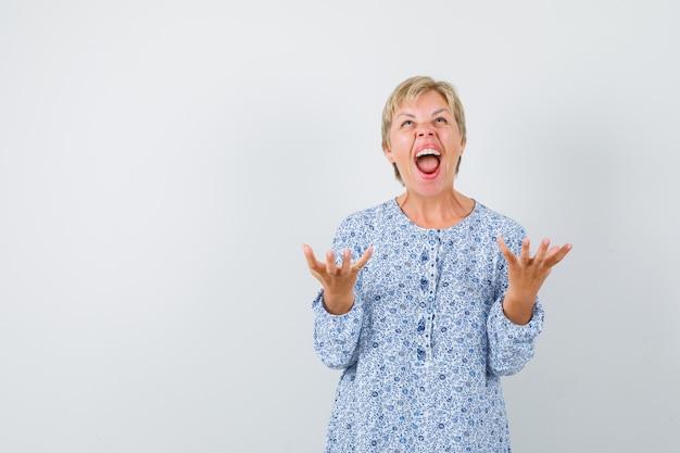 Blonde dame in gemusterter bluse, die hände mit offener handfläche anhebt, während sie schreit und energisch schaut, vorderansicht. freier speicherplatz für ihren text