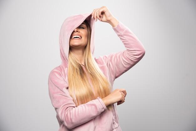 Blonde dame in rosa sweatshirt macht freudige und positive posen, indem sie hoodie an ihrem kopf trägt.