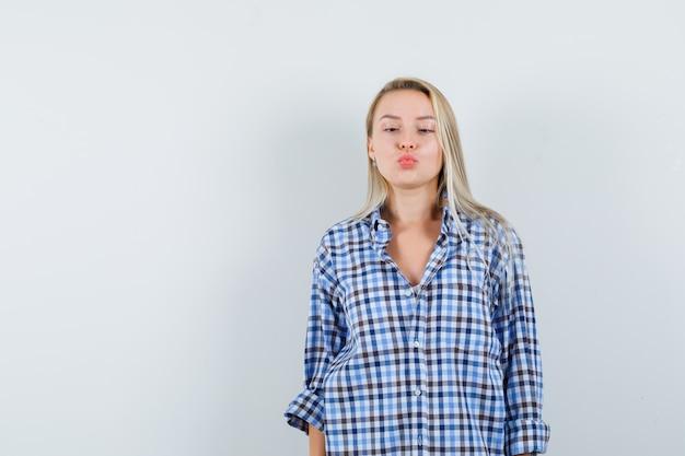 Blonde dame kniff die augen zusammen und schmollte die lippen im karierten hemd