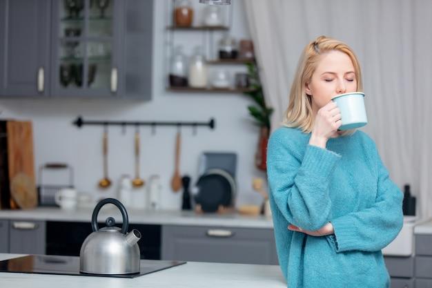 Blonde dame mit tasse kaffee in der küche