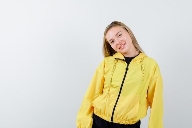 Blonde dame posiert, während sie kopf auf ihrer schulter im trainingsanzug beugt und elegant aussieht. vorderansicht.