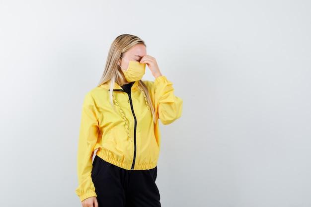 Blonde dame reibt augen und nase im trainingsanzug, maske und sieht müde aus, vorderansicht.