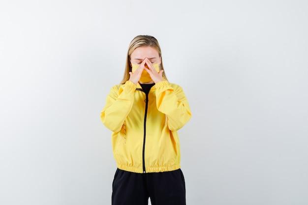 Blonde dame reibt augen und nase in trainingsanzug, maske und sieht müde aus. vorderansicht.