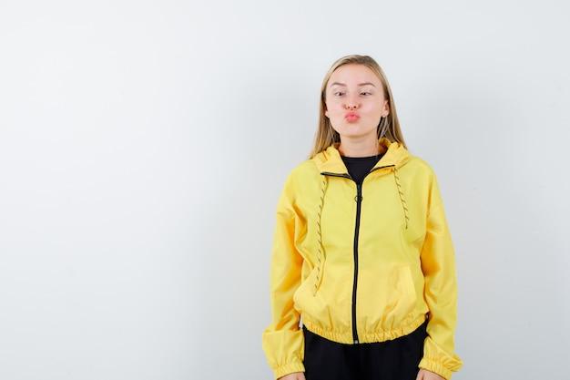 Blonde dame schmollt lippen, blinzelt die augen im trainingsanzug und sieht lustig aus, vorderansicht.