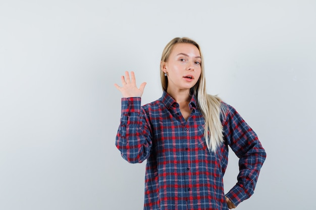 Blonde dame winkt hand, um sich im freizeithemd zu verabschieden und selbstbewusst auszusehen. vorderansicht.