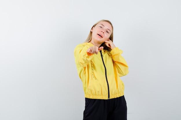 Blonde dame zeigt telefongeste im trainingsanzug und schaut lustig, vorderansicht.