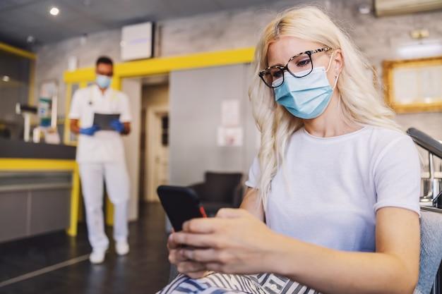 Blonde, die in der halle des labors sitzt und smartphone verwendet, während sie auf ergebnisse wartet
