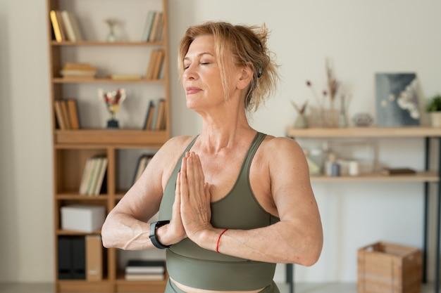 Blonde entspannte reife frau in sportbekleidung, die ihre hände durch brust und augen während der meditation in der häuslichen umgebung zusammengehalten hält