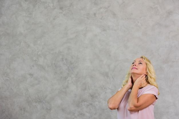 Blonde fällige frau, die oben mit exemplarplatz schaut