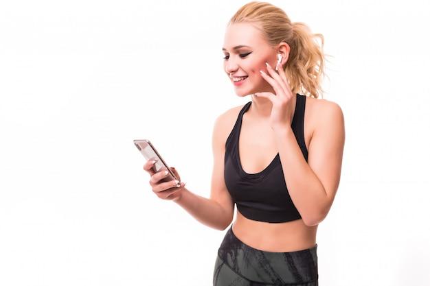 Blonde fitnessfrau, die musik auf kopfhörern lokalisiert auf weiß hört