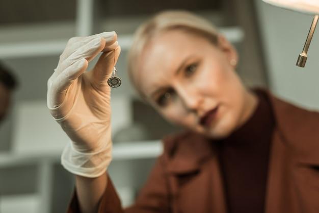 Blonde forensikerin. blonde frau mit rotem lippenstift, der während der ernsthaften suche in wohnungen aufmerksam auf geheimes mikrofon schaut