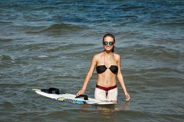 Blonde frau am strand mit surfbrett