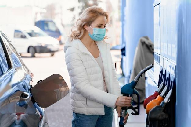 Blonde frau an der tankstelle mit ihrem auto