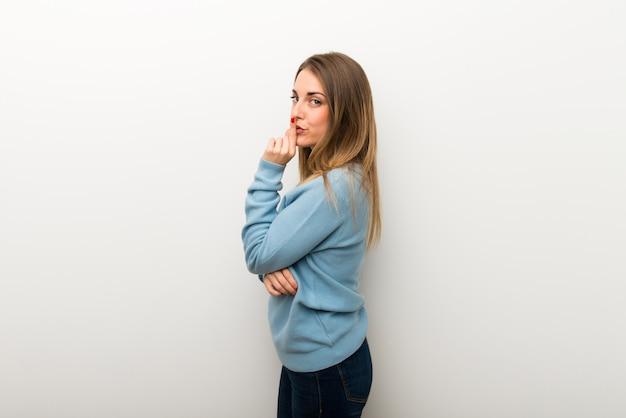 Blonde frau auf dem lokalisierten weißen hintergrund, der ein zeichen des schließens der mund- und ruhegeste zeigt
