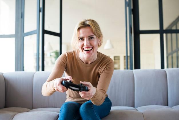 Blonde frau auf der couch, die spielkonsole spielt