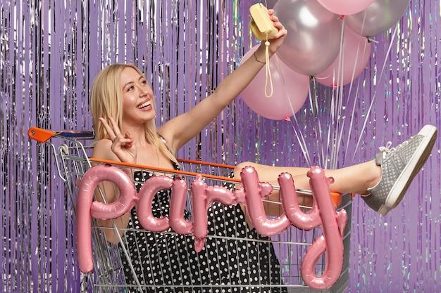 Blonde frau auf der party im einkaufswagen, der luftballons hält