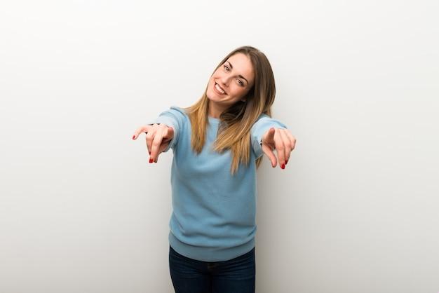 Blonde frau auf lokalisiertem weißem hintergrund zeigt finger auf sie beim lächeln