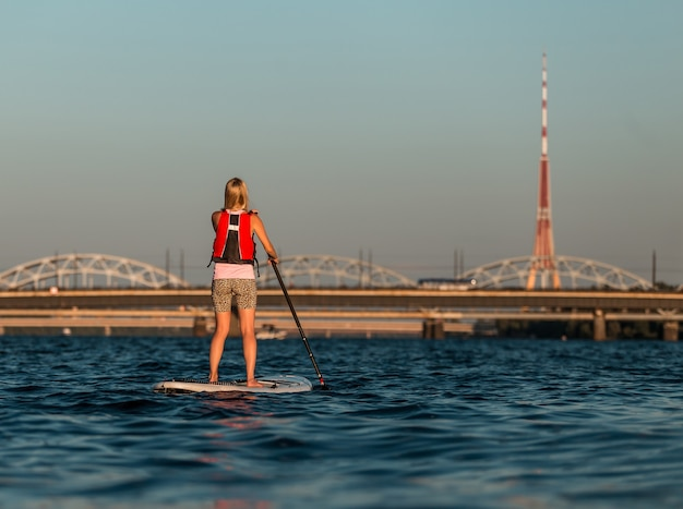 Blonde frau auf paddleboard am fluss daugava, lettland