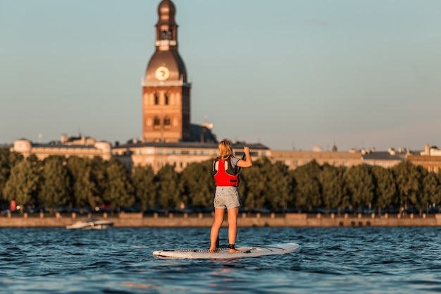 Blonde frau auf paddleboard auf dem hintergrund der altstadt von riga, lettland
