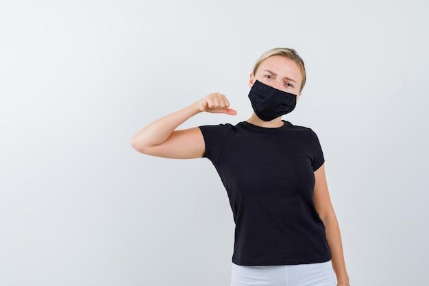 Blonde frau ballt die faust in schwarzem t-shirt, weißer hose, schwarzer maske und sieht ernst aus