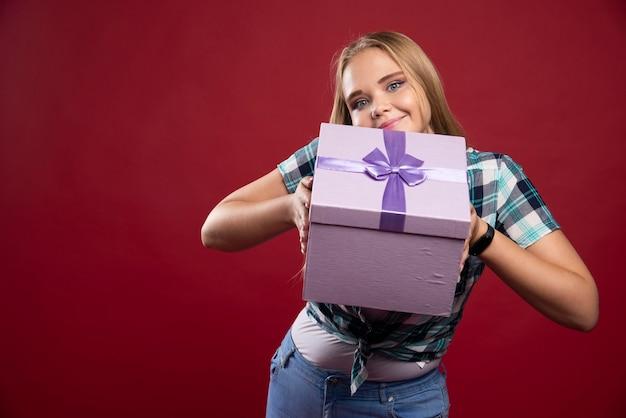 Blonde frau bietet positiv eine geschenkbox an oder teilt ihre mit anderen.