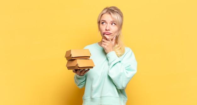 Blonde frau denkt, fühlt sich zweifelhaft und verwirrt, hat verschiedene möglichkeiten und fragt sich, welche entscheidung sie treffen soll