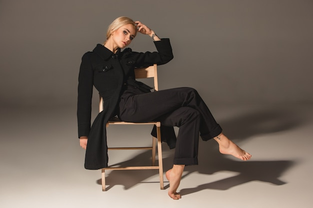 Blonde frau der schönheit auf stuhl