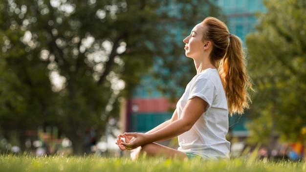 Blonde frau der seitenansicht, die draußen meditiert