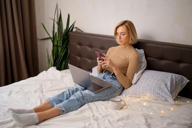Blonde frau des kurzen haares auf weißem bett in jeans mit einem laptop, der smartphone hält.