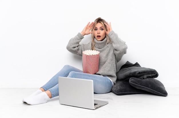 Blonde frau des teenagers, die popcorn isst, während sie einen film auf dem laptop mit überraschungsausdruck sieht
