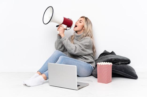 Blonde frau des teenagers, die popcorn isst, während sie einen film auf dem laptop sieht, der durch ein megaphon schreit