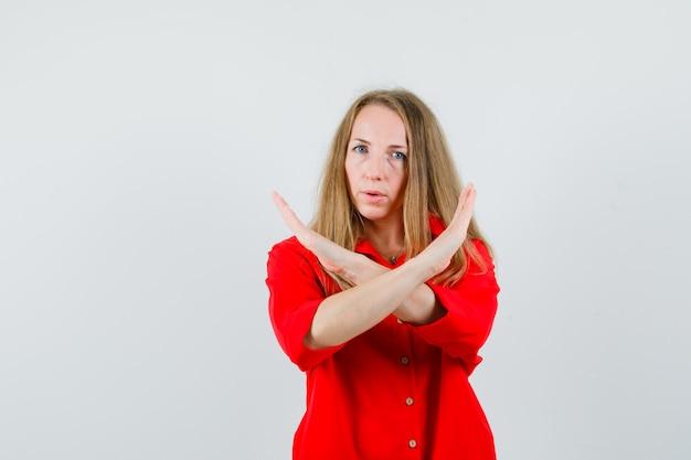 Blonde frau, die ablehnungsgeste im roten hemd zeigt und entschlossen schaut,