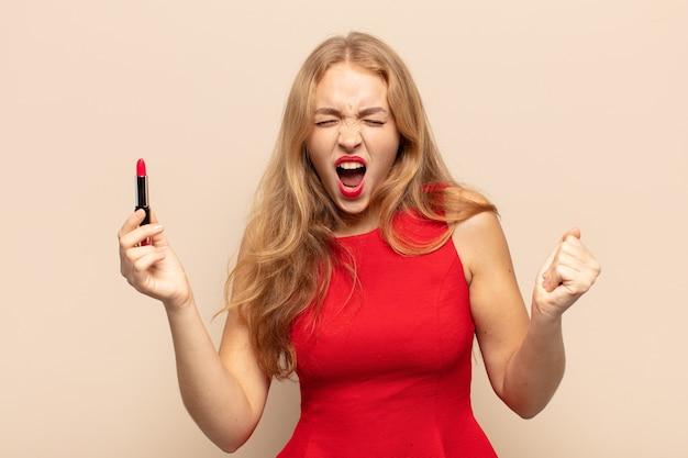 Blonde frau, die aggressiv mit einem wütenden ausdruck oder mit geballten fäusten schreit, um erfolg zu feiern