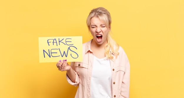 Blonde frau, die aggressiv schreit, sehr wütend, frustriert, empört oder genervt aussieht und nein schreit