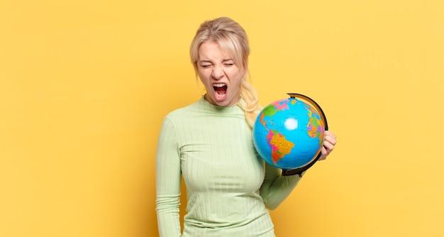 Blonde frau, die aggressiv schreit, sehr wütend, frustriert, empört oder verärgert aussieht, nein schreit