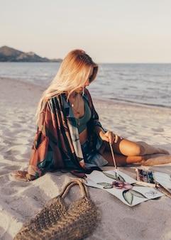 Blonde frau, die aquarellblume durch pinsel auf dem strand zeichnet