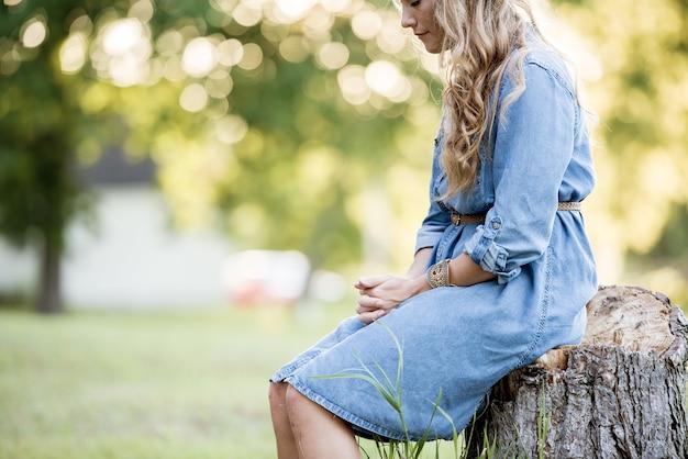 Blonde frau, die auf einem baumstumpf sitzt und in einem garten unter sonnenlicht betet