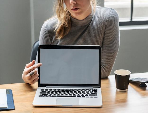 Blonde frau, die auf einen laptopbildschirm zeigt
