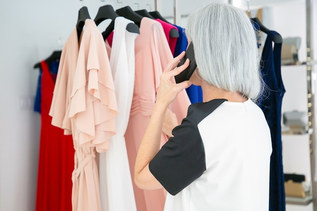 Blonde frau, die auf handy spricht, während sie kleidung wählt und kleider auf gestell im modegeschäft durchsucht. rückansicht. boutique-kunden- oder einzelhandelskonzept