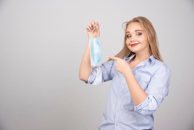 Blonde frau, die auf medizinische maske zeigt