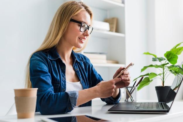 Blonde frau, die auf smartphone arbeitet und einwirkt